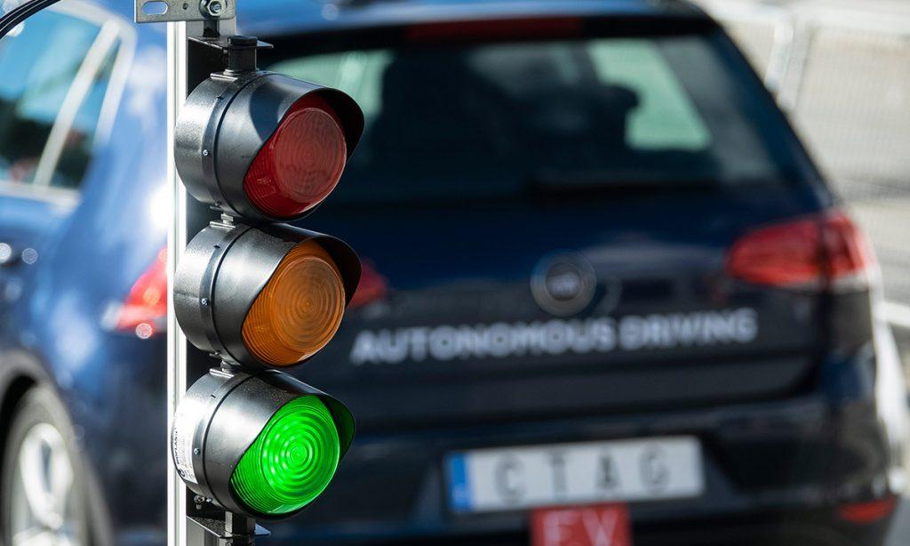 Vehículo autónomo de CTAG, con un semáforo conectado en primer plano.
